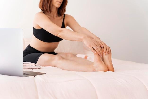 Close-up kobieta rozciągająca nogi w łóżku