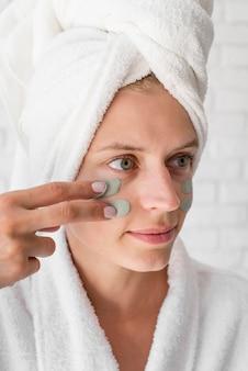 Close-up kobieta stosując środek zaradczy na twarz