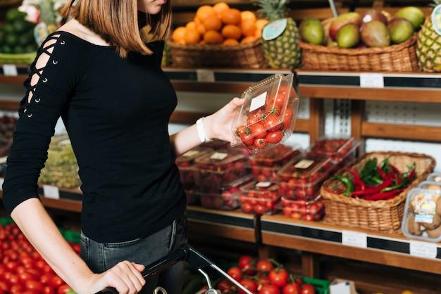 Close-up kobieta trzyma pomidory czereśniowe