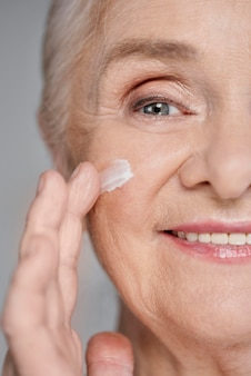 Close-up kobieta za pomocą kremu do twarzy