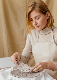 Close-up kobieta zdobienia płyty gliny