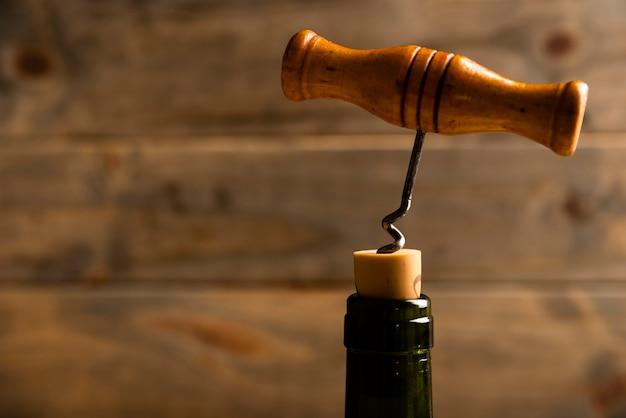Close-up korkociąg z drewnianym tłem