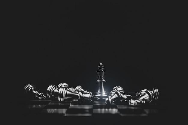 Close-up król szachy stojący zwycięzca ze spadającymi szachami.