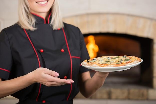 Close-up kucharz pokazuje smaczną małą pizzę.