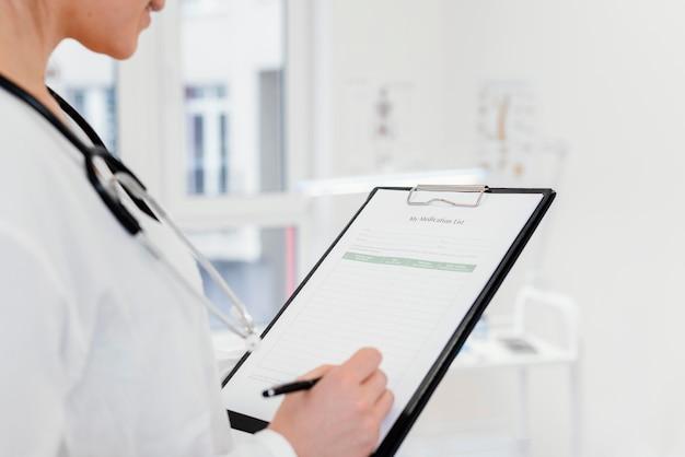 Close-up lekarz pisze informacje