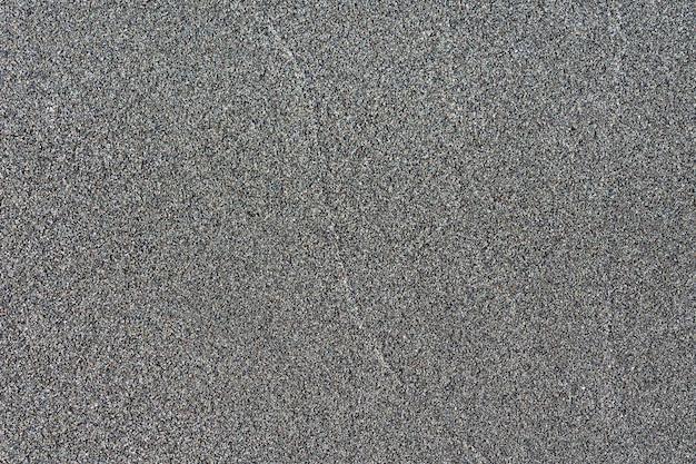 Close-up makro widok powierzchni piasku wulkanicznego w kolorze czarnym. szczegółowa natura tło lub tekstura wzór zrobione w środowisku naturalnym. zwietrzały przez wiele lat, niepowtarzalny, niepowtarzalny efekt teksturowanego wzoru