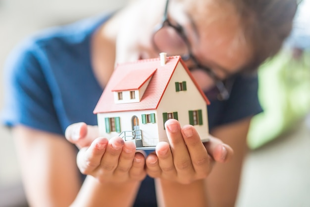 Close-up mały model domu w rękach nastolatki.