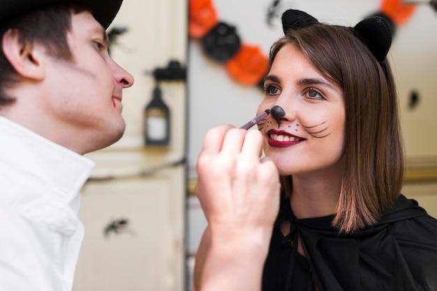 Close-up mężczyzna malowanie twarzy kobiety