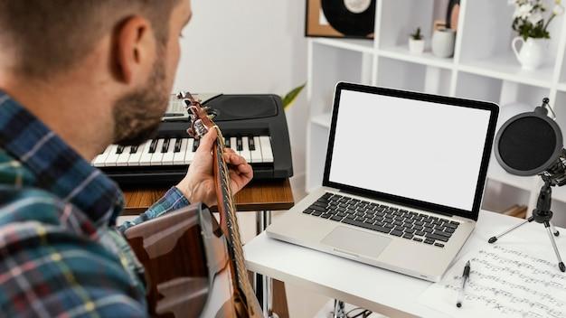 Close-up mężczyzna nagrywa piosenkę z gitarą