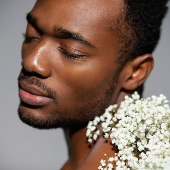 Close-up mężczyzna pozuje z pięknymi kwiatami