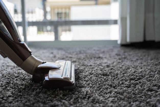 Close-up mężczyzna używa próżniowego cleaner podczas gdy czyścić w pokoju