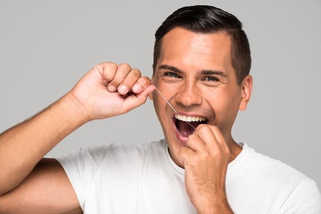 Close-up mężczyzna za pomocą nici dentystycznej