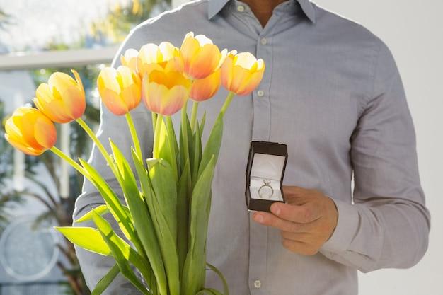 Close-up mężczyzny gospodarstwa pierścionek zaręczynowy i bukiet kwiatów