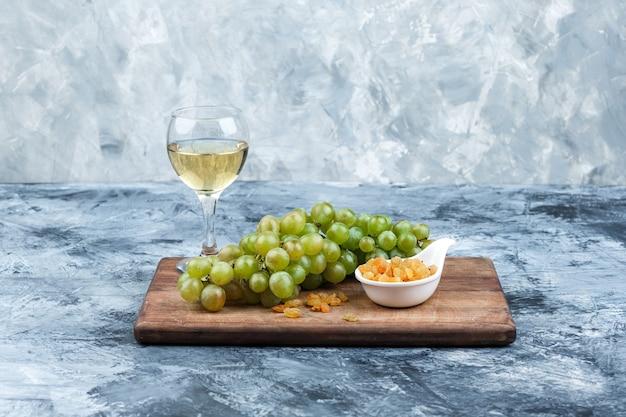 Close-up miska winogron, rodzynek na desce do krojenia ze szklanką whisky na ciemnym i jasnoniebieskim tle marmuru. poziomy