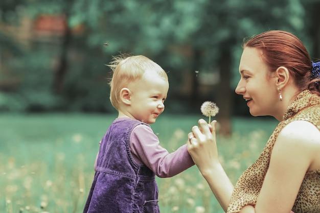 Close up.młoda matka uczy córeczkę dmuchać na mniszka lekarskiego.