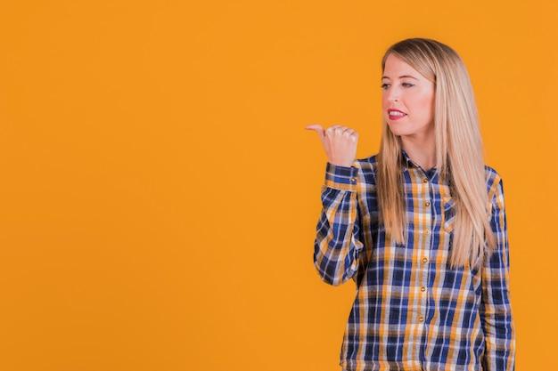 Close-up młodej kobiety pokazując kciuk gest na bok na pomarańczowym tle