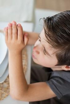Close-up młody dzieciak modli się o pomoc