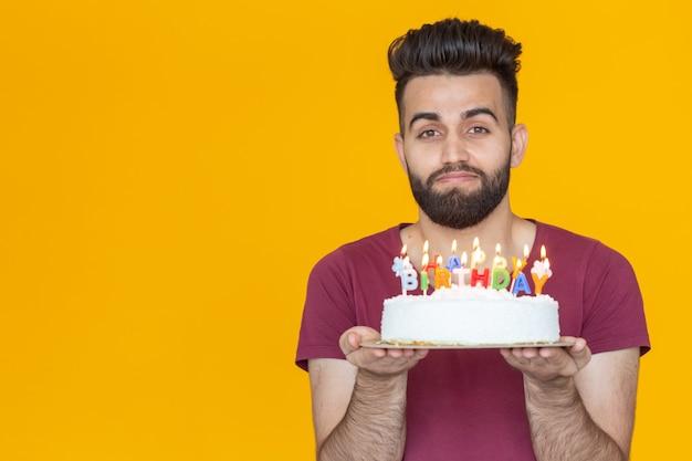 Close-up młody przystojny mężczyzna zdmuchuje świeczkę z płonącego ciasta pozowanie na żółtym tle. koncepcja wakacje.