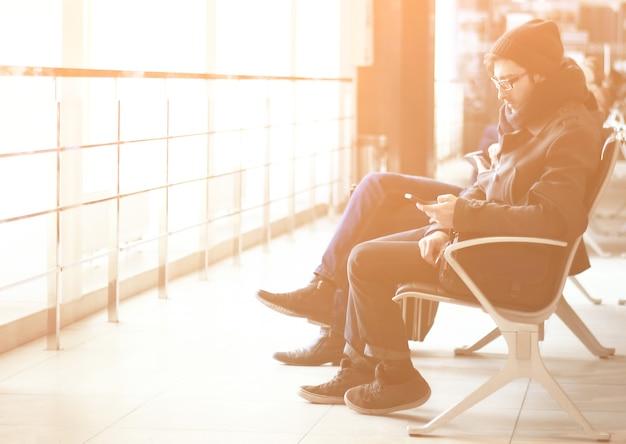 Close up.modern człowiek ze smartfonem siedzący w poczekalni na lotnisku