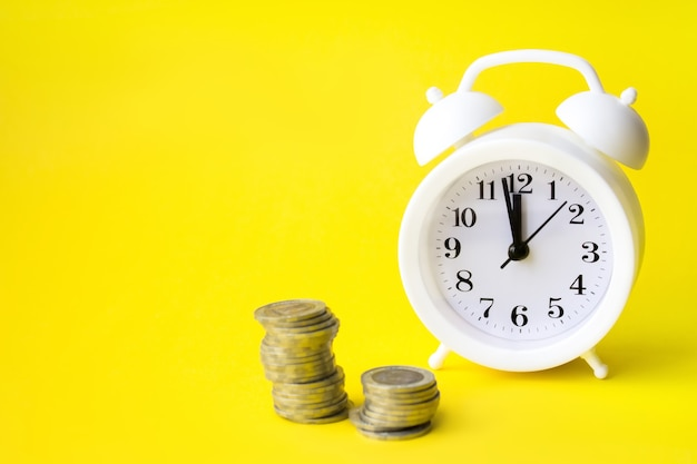 Close-up monet przez budzik na żółtym tle. koncepcja oszczędzania, koncepcja finansów czasu.