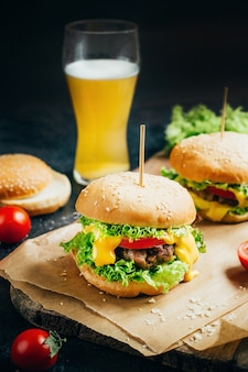 Close-up na hamburger z mi? sem na grillu pomidorów i zieleni na czarnym tle