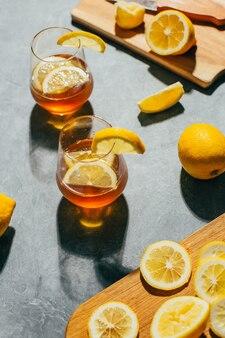 Close-up na kieliszek z koktajlem alkoholowym w szklance z cytryną na szaro