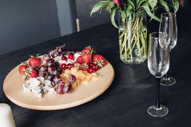 Close-up na pyszne jedzenie talerz pełen przyprawione świeżych jagód, owoców i sera.