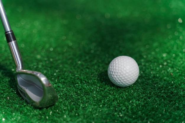Close-up niblick i biała piłka do golfa na zielonej trawie