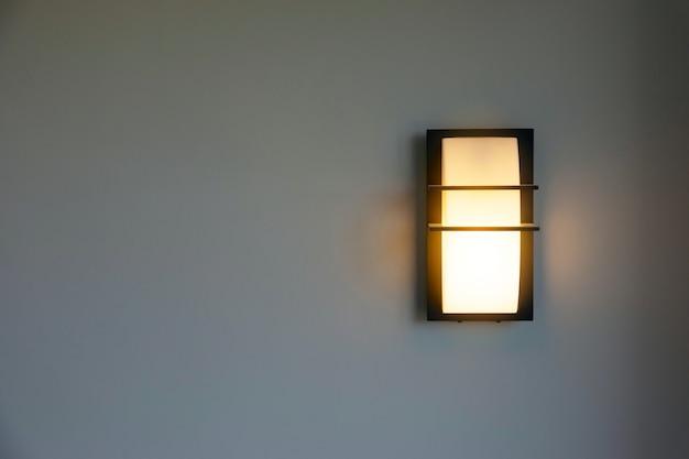 Close-up nowoczesnego projektu ściennego oświetlenia domu na ścianach z białego cementu.