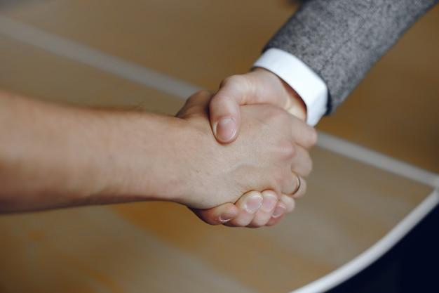 Close-up obraz firmy uścisk dłoni. człowiek stojący za zaufanym partnerem.
