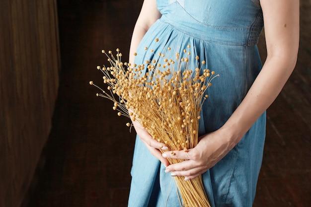 Close-up obraz kobiety w ciąży dotykając jej brzucha rękami