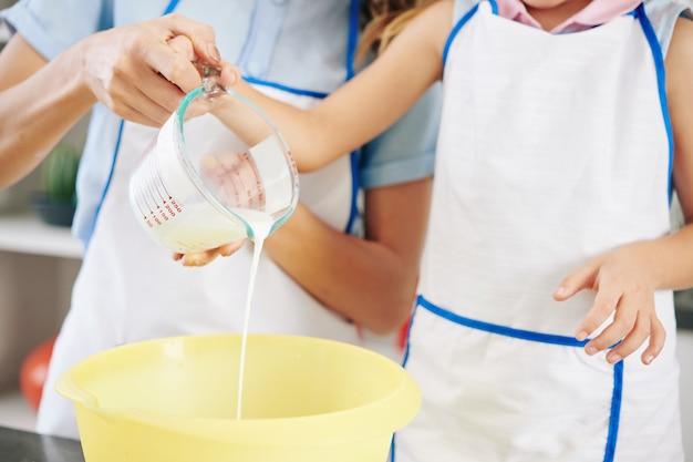 Close-up obraz matki i córki, odlewanie świeżej zimnej śmietany w misce podczas robienia słodkiego lukier