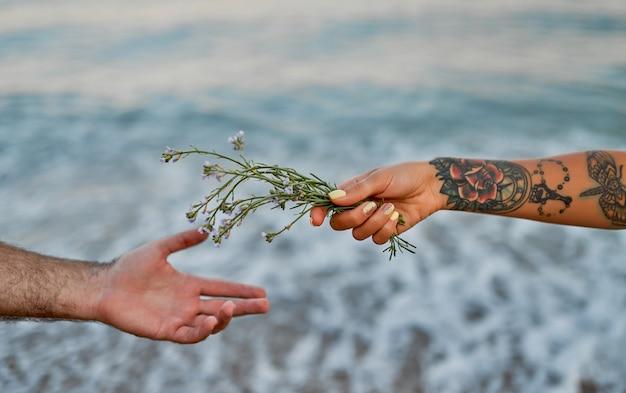 Close-up obraz męskich i żeńskich rąk z kwiatami nad morzem.