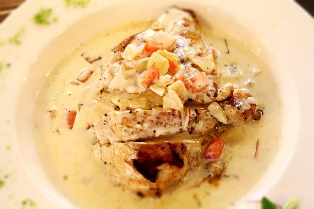 Close-up obraz pieczonego kurczaka w sosie serowym śmietanowym zwieńczona kotlety ziemniaczane i carro