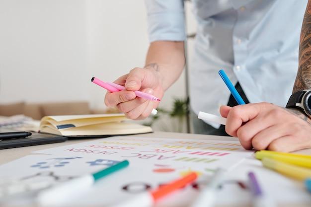 Close-up obraz projektanta graficznego rysującego szkice logo firmy z kolorowymi flamastrami