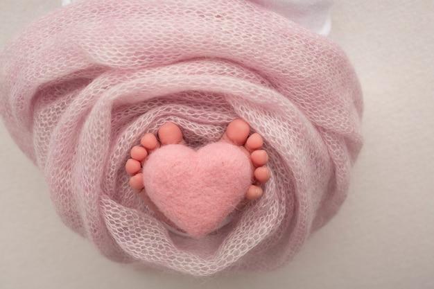 Close-up obraz stóp noworodka na różowym kocu. różowe dzianinowe wełniane serduszko w palcach noworodka.