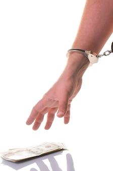 Close-up of mans ręcznie w zamkniętych kajdankach metalowych gotowy do pobrania gotówki dolarów amerykańskich izolowanych na białej ścianie. nielegalne zarabianie pieniędzy, przekupywanie, korupcja, przestępstwa i kary