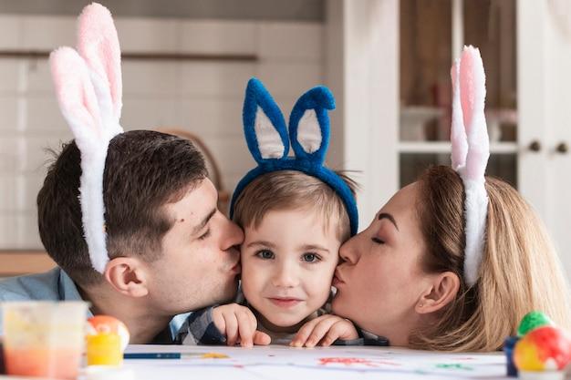 Close-up ojciec i matka całuje małego chłopca