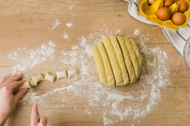 Close-up osoby cięcia ciasta do przygotowania świeżych włoskich makaron gnocchi