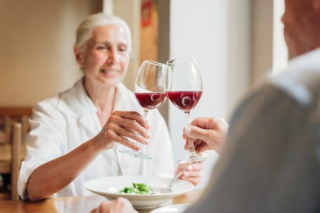 Close-up para szczęk szklanki z czerwonym winem