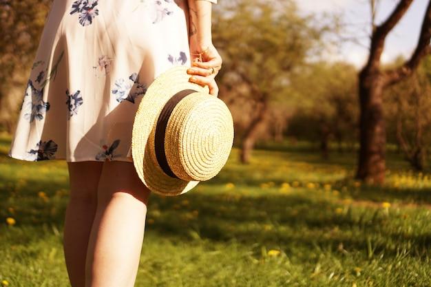 Close-up photo - dziewczyna w słomkowym kapeluszu trzyma kapelusz w dłoniach w letnim ogrodzie