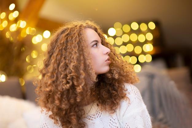 Close-up piękne młode kręcone włosy kobiety twarz portret na powierzchni światła bokeh koloru żółtego