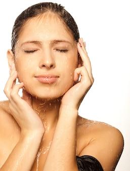 Close-up pięknej mokrej twarzy kobiety z kropli wody