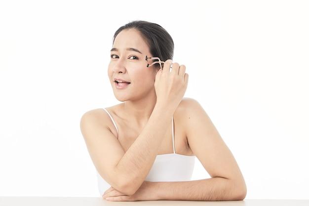 Close-up piękno azjatycka kobieta z idealnym makijażem nago. patrząc na bok, machając rzęsami specjalnym przyrządem. salon piękności. głowa i ramiona, profil, studio, wnętrze