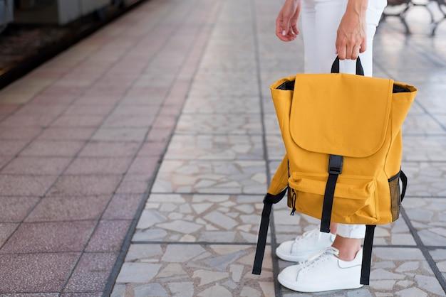 Close-up plecak i dziewczyny nogi w stacji kolejowej