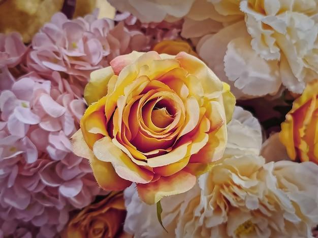 Close-up pomarańczowa róża i inne różowe białe kwiaty zdobione na uroczystości