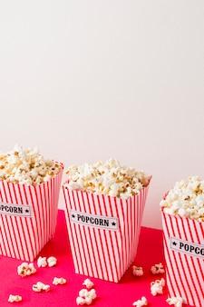 Close-up popcorns w pasiastych pudełkach na różowym biurku przeciw białej ścianie
