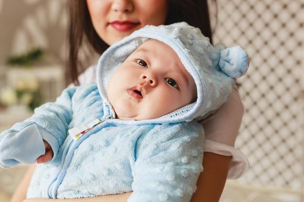 Close-up portret 2 miesiąca życia noworodka rasy mieszanej azji chłopca i jego matki. naturalne oświetlenie wewnętrzne. fajne dźwięki.
