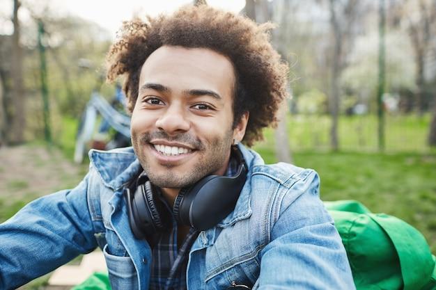 Close-up portret atrakcyjnego, nieogolonego ciemnoskórego mężczyzny z fryzurą afro, uśmiechającego się i wyrażającego szczęście, siedząc w parku, ciesząc się ładną pogodą i słuchając muzyki.