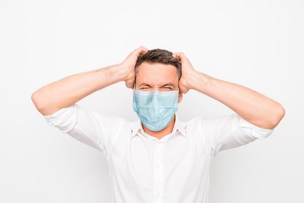 Close-up portret atrakcyjny zły zły szalony facet ubrany w niebieską gazę maskę choroba choroba choroba paniki skażenie na białym tle na jasnobiałym tle